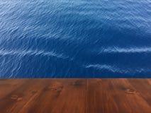 Старая таблица на голубой предпосылке моря, деревянная таблица палубы коричневого дуба деревянная стоковое фото