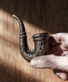 Старая труба дыма в мужской руке стоковые фото