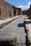 Старая улица руин с 2 туристами в Помпеи, Италии Античная дорога в итальянском древнем городе Ориентир ориентир Помпеи стоковая фотография