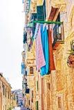 Старая улица с традиционными домами и балконами Валлеттой стоковое изображение