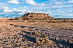 Старая церковь самана установила в ландшафт пустыни под Black Mesa и Sangre de Cristo Горой около Санта-Фе, Неш-Мексико стоковая фотография