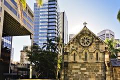 Старая церковь со зданиями и деревьями города стоковая фотография