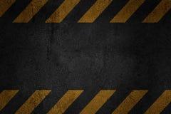 Старая черная grungy поверхность asfalt с желтыми предупреждающими нашивками Стоковые Фото