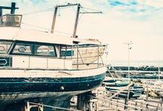 Старая шлюпка в гавани Acitrezza со шлюпками fisher рядом с островами циклопов, Катанией, Сицилией, Италией стоковые фотографии rf