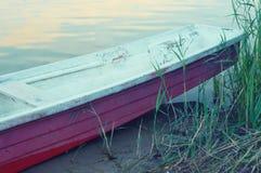 Старая шлюпка отдыхая на береге озера стоковые изображения rf