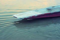 Старая шлюпка отдыхая на спокойной воде стоковая фотография