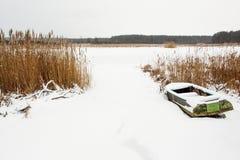 Старая шлюпка на береге замороженного реки с тростниками Стоковое фото RF