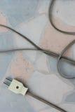 Старая электрическая штепсельная вилка на поле Стоковые Изображения