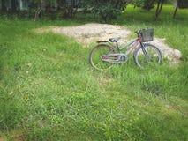 Старая Grungy автостоянка велосипеда в поле зеленой травы Стоковые Фотографии RF