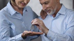 Старея мужской давая ключ дома к усмехаясь даме, приобретению недвижимости, ипотеке стоковая фотография