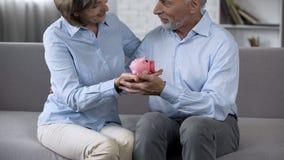 Старея пары сидя на кресле с копилкой, сохраняя деньгами для мечты, будущего стоковое фото