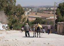 Старик водя его осла бакалеи гружёного далеко от еженедельного открытого рынка berber короткий путь от Essaouira в Марокко - Land стоковая фотография
