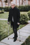 Старик в костюме идет с ходоками для взрослых стоковое фото rf