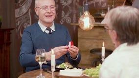 Старик делая предложение к его партнеру на романтичном обедающем видеоматериал