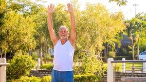 Старик делает повороты тренировок утра праволевые в парке