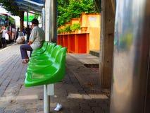 Старик ждать на автобусной остановке, перед университетом KMUTNB Стоковые Изображения RF