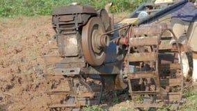 Старик используя небольшой трактор для того чтобы вспахать ферму для того чтобы отрегулировать почву для засаживать видеоматериал