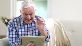 Старик используя видео- болтовню на таблетке сток-видео