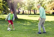 Старик и мальчик играя футбол на парке лета стоковое фото rf