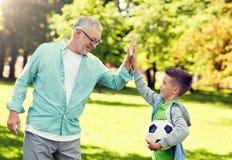 Старик и мальчик с футбольным мячом делая высоко 5 стоковая фотография