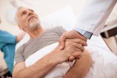 Старик лежит на кроватке в медицинской палате, и рядом с ним стойки доктор Доктор трясет руку ` s старика Стоковое Изображение