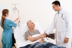 Старик лежит на кроватке в медицинской палате, и рядом с ним стойки доктор Доктор трясет руку ` s старика Стоковое фото RF