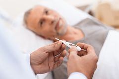 Старик лежит на кроватке в медицинской палате Рядом с ним доктор Доктор измеряет температуру старика Стоковое Фото