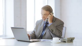 Старик при портативный компьютер принимая телефонный звонок видеоматериал