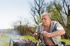 Старик проверяя если зажаренное мясо Хорошо сварено стоковое фото rf