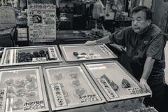 Старик продавая морепродукты на японском рыбном базаре стоковые фотографии rf