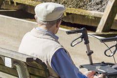 Старик сидит на стенде в парке Стоковое Изображение