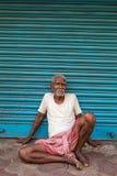 Старик сидя около сини закрывает в Kolkata, Индии стоковые фото