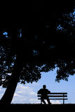 Старик сидя самостоятельно на скамейке в парке под деревом Стоковые Изображения RF