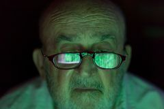 Старик смотря прорубленный экран компьютера Стоковая Фотография