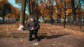 Старик с книгой снаружи в парке акции видеоматериалы
