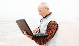 Старик с тетрадью на пляже стоковые фотографии rf