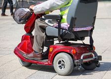 Старик с электрической кресло-коляской на улице стоковое фото rf