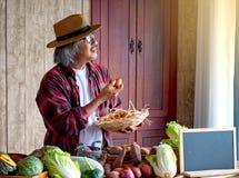 Старик с яйцом владением шляпы и корзиной яя и взгляд к окну со светом дня, думают об его меню для варить сегодня с стоковые фото