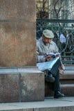 Старик читая газета новостей памятником Питер Tchaikovsky Туристы идя вокруг Москвы стоковое изображение rf