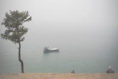 Старик wathing на сиротливой шлюпке на Lake Baikal под туманом Стоковые Фотографии RF