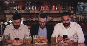 3 старого друга используя смартфоны сидя в пабе пива Сообщение, концепция наркомании интернета акции видеоматериалы