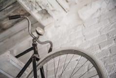 Старое белое whist велосипеда на белой каменной стене Стоковое Изображение RF