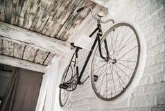Старое белое whist велосипеда на белой каменной стене Стоковые Фотографии RF