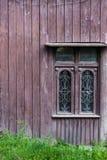Старое винтажное окно на деревянном доме абстрактный коричневый цвет предпосылки выравнивает изображение Зеленая трава на дне Стоковые Изображения RF