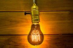 Старое винтажное Edison& x27; электрическая лампочка s накаляя на предпосылке деревянных планок стоковые изображения rf