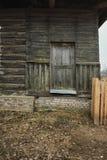 Старое выдержанное деревянное окно с шарнирами на старом деревянном разрушанном доме стоковые фотографии rf