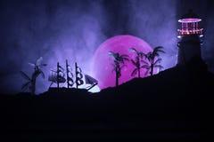 Старое деревянное плавание военного корабля к ноча близко к маяку или маяку и паруснику Темная туманная предпосылка Селективный ф Стоковая Фотография RF