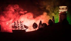 Старое деревянное плавание военного корабля к ноча близко к маяку или маяку и паруснику Темная туманная предпосылка Селективный ф Стоковое Изображение