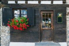 Старое деревянное окно с штарками и цветки приближают к старому деревянному doo Стоковые Изображения