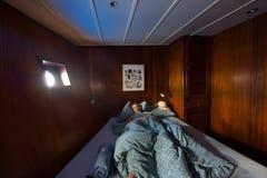 Старое деревянное interor кабины корабля, спать женщина в кровати стоковое фото